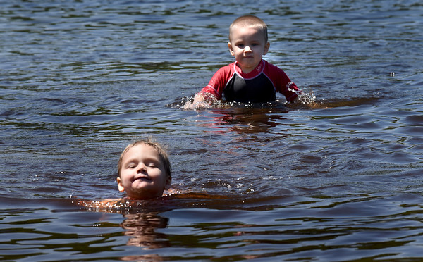 BRYAN EATON/Staff Photo. Kayleigh Deragon, 4, left, and her cousin Hunter Perkins, 3, both of Seabrook ply the waters at Lake Gardner Beach on Wednesday afternoon. Rain comes in for Thursday, but Friday and Saturday are forecast to be stellar.