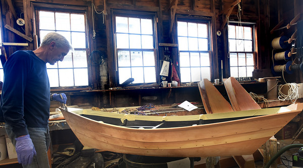 BRYAN EATON/Staff Photo. Bart Bauer of Wakefield paints a model boat which is the bottom part of an oyster bar that was commissioned by Camden Yard in Baltimore at Lowell's Boat Shop in Amesbury. He's one of over 15 volunteers, known in house as woodworkers, that meet twice a week and work on projects to help fund the working museum.