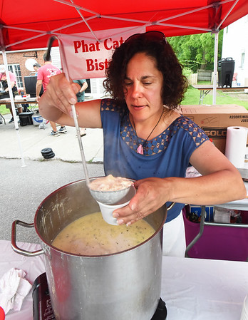 BRYAN EATON/Staff photo. Phat Cats Bistro co-owner Christina Johnson serves up fish chowder, one of several Amesbury restaurants feeding the crowd at the Block Party.