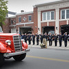 BRYAN EATON/Staff Photo. Firefighters in front of the Amesbury Fire Station salute as the body of Robert Fredette is taken to Holy Family Parish for his funeral on Thursday. Fredette joined the Amesbury Fire Department in 1954 and retired in 1990 as deputy chief.