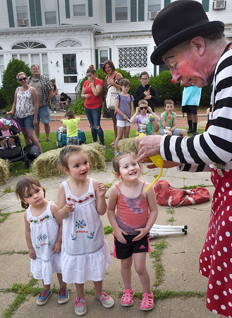 BRYAN EATON/Staff photo. After helping him with part of his act, Davey The Clown made a special balloon inside a balloon for these friends at the Amesbury Days Block Party. From left, Melanie, 3, and Samantha Spaulding, of Merrimac, and Lydia D'Andrea, 4, of Amesbury.