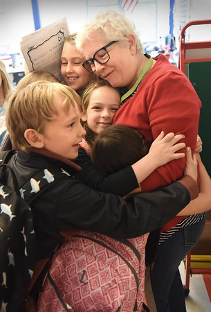 BRYAN EATON/Staff Photo. Bresnahan School first grade teacher Sue Harrington gets hugs from her students as they left class on Thursday morning. It was las the last day of classes at Newburyport schools.