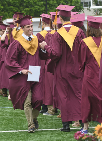 JIM VAIKNORAS/Staff photo Newburyport graduate Christopher Blangiardi give a classmate a fist bump after getting his diploma at World War Memorial Stadium in Newburyport Sunday .