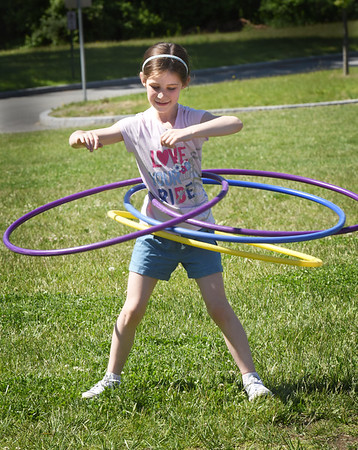 BRYAN EATON/Staff Photo. Kendall Martin, 8, keeps twirling four hula hoops to keep them from falling on Friday morning. She was at one of the stations for Field Day at the Bresnahan School in Newburyport.