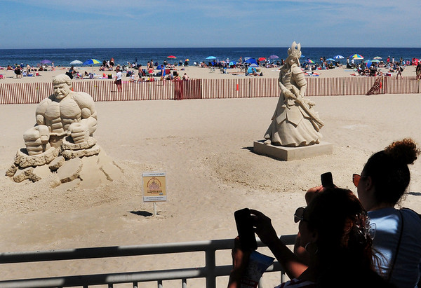 """BRYAN EATON/Staff Photo. People take cell phone photos of the displays from this weekend's Hampton Beach Master Sand Sculpting Classic including Groveland resident Justin Gordon's """"Hulk in 3-D at left."""