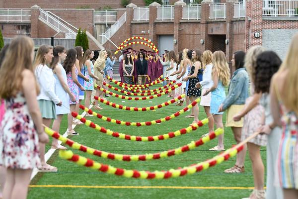 """JIM VAIKNORAS/Staff photo Newburyport seniors enter graduation under the """"Junior Arch of Roses"""" at World War Memorial Stadium in Newburyport Sunday ."""