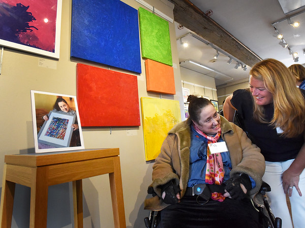 BRYAN EATON/Staff Photo. OpArt coordinator and instructor Jenna Signore, right, talks to Opportunity Works client Karen DeSantis in front of her work at the OpArt opening reception at the Newburyport Art Gallery. The event is a highlight for the 35 artists from the Newburyport and Haverhill Opportunity Works programs and a special celebration for families and friends to celebrate their artistic achievements.