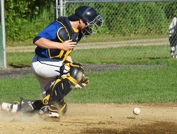 BRYAN EATON/Staff Photo. Rowley Rams catcher Lewi L'heureux scrambles for the ball as the Ipswich player made it home.