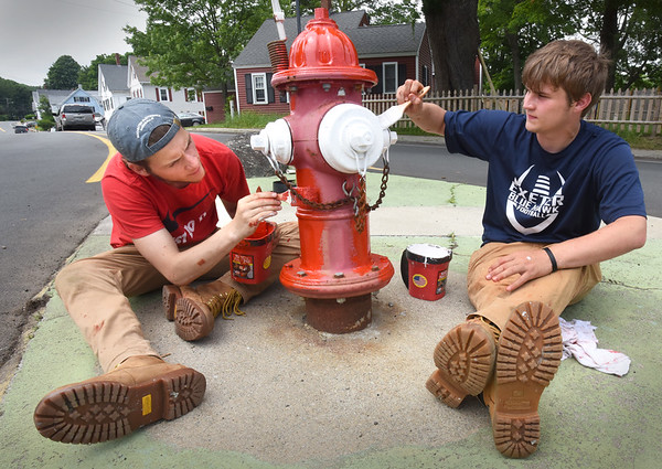BRYAN EATON/Staff Photo. Jared Benevento, left, and Jake Hamel were painting fire hydrants along Whitehall Road in Amesbury, this one at the intersection with Friend Street, on Wednesday afternoon. Two 2019 graduates of Amesbury High School are working at the Amesbury DPW for the summer.