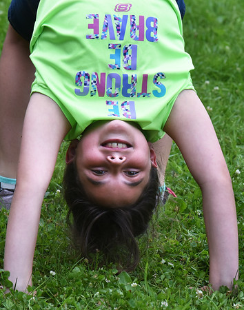 """BRYAN EATON/Staff Photo. Youngsters got to spend time in the playground on Tuesday before the rain appeared, Serenity SIlva, 9, and her friends attempting """"back walkovers."""" They later went to Hodgies Too in Salisbury for some ice cream."""