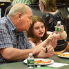 BRYAN EATON/Staff Photo. Bill Ginivan of Amesbury and McKayla Hachey, 9, enjoy a lunch of pizza, carrot sticks, Oreo cookies and bottle water at the Cashman School in Amesbury the Growing Friendships Program between the school and the Amesbury Senior Center. The third-graders went to the Senior Center last month to interview seniors about their lives and wrote a book about them which they presented at the lunch on Monday.
