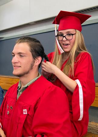 JIM VAIKNORAS/Staff photo Amesbury High School senior Bianca DeMott ties a braid in classmats Jarrod Benevento's hair just before graduation Friday night.