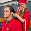 JIM VAIKNORAS/Staff photo Amesbury High School senior Bianca DeMott ties a braid in classmats Jarrod Benevento's hair just before graduation Friday night.