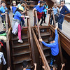 BRYAN EATON/Staff Photo. Third-graders from the Tilton School in Haverhill go down the steep steps facing backward on the Nao Santa Maria.