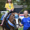 BRYAN EATON/Staff photo. Lydia Broyles of J & J Pony Rental of Groveland leads Lindsay Longacre, 9, of Amesbury on Peter Pan in front of the Amesbury Public Library.