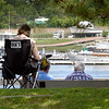 BRYAN EATON/Staff Photo. Either with their own chair, or benches on the boardwalk on Newburyport's waterfront, people took in views of the boats docked or moored in the Merrimack River on a sunny Monday morning. After some overnight and morning rain, the sun is forecast to reappear this afternoon.