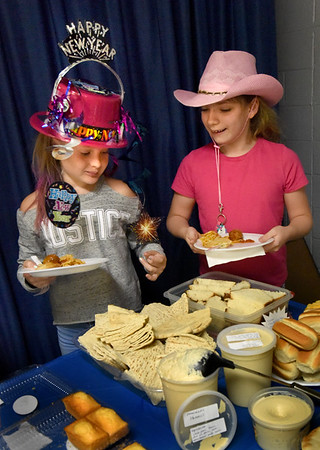BRYAN EATON/Staff Photo. Amesbury Elementary School fourth-graders held an Immigration Luncheon culminating their studies of different countries and their cultures, customs and cuisine. Checking out the the different offerings from around the world provided by parents, are Hope Shanahan, left, and Abby Lamott, both 10, wearing differents hats as it was Crazy Hat Day too.