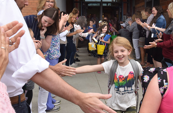 BRYAN EATON/Staff Photo. Students head out of the Bresnahan School for the last day of classes as teachers applaud on Thursday. Today is last day of classes in the Triton district followed by Amesbury on Monday.
