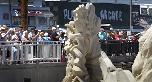 BRYAN EATON/Staff Photo. A constant stream of people moved along the sidewalk at Hampton Beach on Monday afternoon photographing the sand sculptures from this weekend's Hampton Beach Master Sand Sculpting Classic.