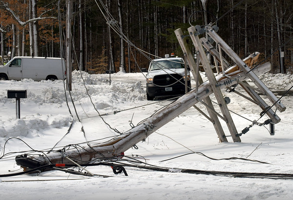 BRYAN EATON/Staff photo. This toppled utility pole was still blocking Ferry Road at Spring Lane in Newburyport early Wednesday afternoon after crashing sometime early Tuesday evening. Much of the area around there, near Maudslay State Park lost power.
