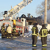 BRYAN EATON/Staff photo. Firefighters had to contend with icy ground conditions as they battled the fire.