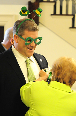 JIM VAIKNORAS/Staff photo Cynthia Costello pins a corsage on Representative James Kelcourse at the Link House Inc's 15th annual St. Patrick' Day Luncheon at the Masonic Temple in Newburyport Friday.