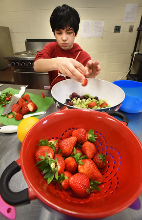 BRYAN EATON/Staff photo. Sebastian Dematteo, 12, of Amesbury makes a fruit salad in the cooking class at the Boys and Girls Club in Salisbury on Tuesday, the theme being breakfast foods, where students also made breakfast burritos and crepes. The club is holding an open house tonight from 6:00-7:30 p.m. for parents to tour the facility along with potential new members and their parents.