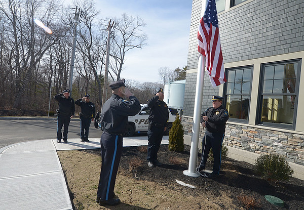 JIM VAIKNORAS/Staff photo Salisbury officers Jayson Davis, Bruce Dow, Pat Szymkouski, and Sqt Steve Sforza, salute as Chief Thomas Fowler raises the flag for the first time at the new Salisbury Police Station on Beach Road Friday afternoon. The station recieved it occupancy permit and officially moved in Friday.