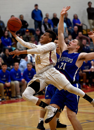 JIM VAIKNORAS/Staff photo Newburyport's George Mwai glides to the basket against  Bedford player at Tewskbury high school Tuesday night.