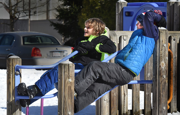 BRYAN EATON/Staff photo. Oliver Peters, 8, left and Andrew Scorzoni, 10, lounge around some playground equipment on Monday afternoon. They were at the Amesbury Recreation Department's afterschool program at Amesbury Elementary School where they took activities outside for the nice weather.