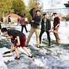 BRYAN EATON/Staff photo. Members of the Newburyport High School tennis team clear off the snow at courts at Atkinson Common on Monday after noon. Coach Ben Laing was hoping that Tuesday's warm temperature would finish the job so they can practice there, their first game not until April vacation.