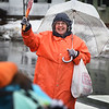 BRYAN EATON/Staff photo. Newburyport Schools crossing guard Peggy Lysik smiles at students as they cross Greenleaf Street at Pond Street while wearing a heavy duty raincoat and holding an umbrella. Rain is forecast to continue Tuesday with clearing on Wednesday.