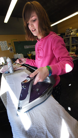 BRYAN EATON/Staff photo. Rory Ciarametaro, 11, irons a piece of fabric before putting to a sewing machind to make a pillow case. She was in sewing class at the Boys and Girls Club in Salisbury which is taught by Judy Gaffney three times a week.
