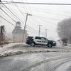 BRYAN EATON/Staff photo. Plum Island Turnpike was blocked to traffic at one point Tuesday afternoon as several utitlity poles were were leaning over the roadway creating a hazard near the Joppa Flats Audubon Center.