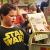 BRYAN EATON/Staff photo. Daniel Medina, 9, checks out books on Star Wars, obviously a fan of the box office hits at the Bresnahan School Book Fair. Students were looking through books they liked, noting the price, then deciding later what books to buy which raises money for the school's library to purchase more books.