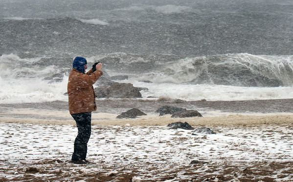 BRYAN EATON/Staff photo. Jeremiah Murphy of Plum Island and Danville, N.H. with the wind at his back takes photos of the surf on the island an hour before Tuesday's high tide.