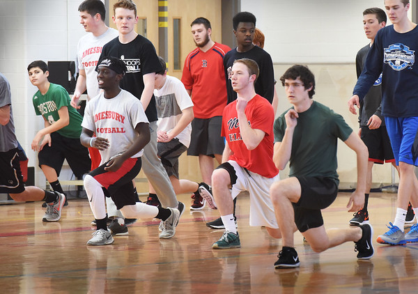 BRYAN EATON/Staff photo. The Amesbury High School boys track team move along doing knee-bends at practice.