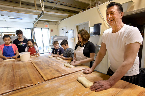 BRYAN EATON/Staff photo. Annarosa's Bakery owners Bill Malatesta, right, and Jane Kenny, back, left, start youngsters off in the basics of breadmaking, in this case a French baguette. Several times a year a group from the Boys and Girls Club come to the Salisbury bakery to make some items they can take home with them while learning the process.
