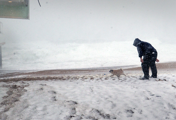 BRYAN EATON/Staff photo. Greg Harden of Salisbury with his dog Oliver at Salisbury Beach as waves crash ashore at Salisbury Beach Center during high tide Tuesday afternoon. The waves did not breach over to Broadway.