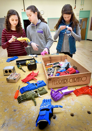 BRYAN EATON/Staff photo. Nock Middle School students in Technology and Engineering are making plastic hands and gloves for people with missing fingers and hands. Working on some in free time are, from left, Lila Sava, 13, Kate Lucy, 14, and Lara Roelofs, 14.