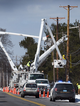 BRYAN EATON/Staff photo. Utility crews from South Carolina replaced the poles that were bent over the Plum Island Turnpike during Tuesday's storm. The area was just west of the Plum Island Airfield.