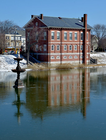 JIM VAIKORAS/Staff photo The Swan Fountain and the Newburyport Superior Court House are reflected in a layer of thin ice on the Frog Pond at the Bartlet Mall in Newburyport Sunday.