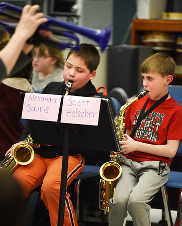 BRYAN EATON/Staff photo. Alexander Sauris, left, and Scott Holscher, both, 9, practice the Star Wars theme song under the direction of Deb Walton in the afterschool beginner's band. They are rehearsing for their upcoming Spring Concert on May 3.