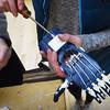 BRYAN EATON/Staff photo. Lara Roelofs, 14, screws in components of a glove.
