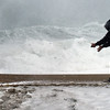 BRYAN EATON/Staff photo. Greg Harden of Salisbury calls for his dog Oliver at Salisbury Beach as waves crash ashore at Salisbury Beach Center. The surf never made it over to Broadway during the high tide.