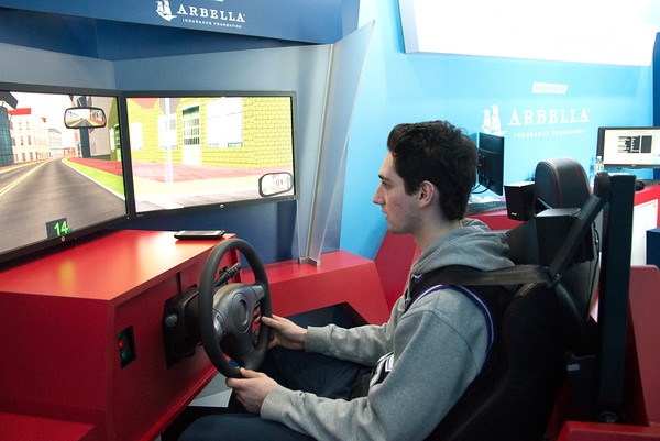 JIM VAIKNORAS/Staff photo Newburyport high junior Harry Dovee takes a drive in a distracted driving simulator at the school Friday.