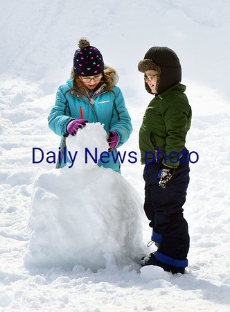 BRYAN EATON/Staff photo. Sydney Richards, left, and Keelan Pothier, both 8, work on making a snowman during recess at Amesbury Elementary School on Thursday. The snow was perfect for the project the melting temperatures making it sticky and easy to shape.