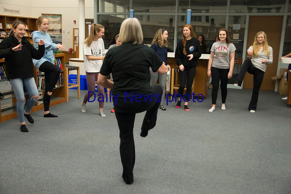 JIM VAIKNORAS/Staff photo Barbara Tilden demonstrates a tia chi pose to a group of Newburyport high school students who are planning a trip to China.