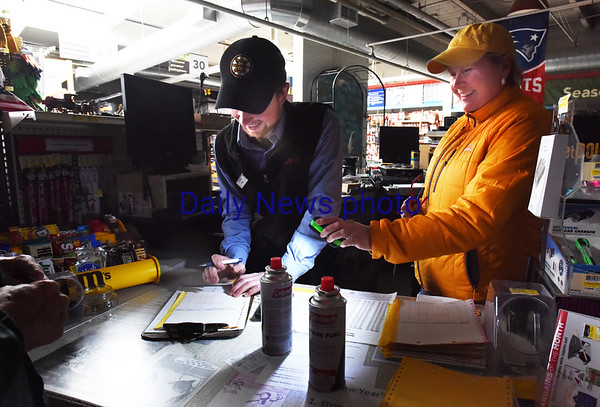 BRYAN EATON/Staff photo. Lisa Kelly of Kelly's Hardware in Newburyport holds a light for Sam Tocci as he fills out a receipt for a customer. The store was selling many batteries, lamps, fuel and bundled firewood.