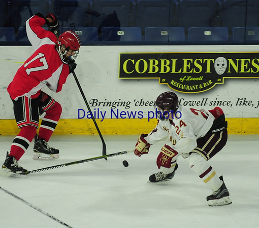 JIM VAIKNORAS/Staff photo  Newburyport's Thomas Greene knocks the puck away from Winchester's James Kelly at the Tsongas Center in Lowell Thursday night.